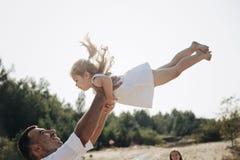 愉快的白种人获得爸爸和他的小的女儿乐趣 父亲投掷白色礼服的甜女儿在天空中 库存照片
