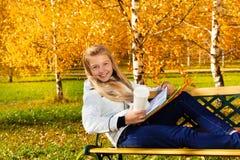 愉快的白肤金发的女孩用咖啡和课本 库存照片