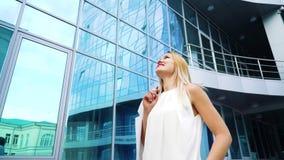 愉快的白肤金发的妇女低角度射击通过摩天大楼镜子表面的时髦的成套装备的  股票视频