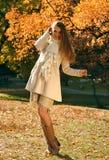 愉快的白肤金发的妇女在秋季公园 免版税库存照片