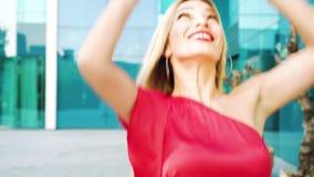 愉快的白肤金发的妇女在街道上跳舞并且跟随移动的照相机 股票视频