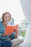 愉快的白肤金发的妇女坐她的拿着书的长沙发 免版税库存照片