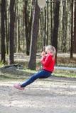 愉快的白肤金发的少年女孩在红色跳和乘坐下来与橡皮筋的夹克和蓝色牛仔裤穿戴了对于儿童wa的` s操场 免版税库存图片
