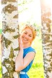 愉快的白肤金发的拥抱桦树树干在公园 免版税库存照片