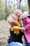 愉快的白肤金发的母亲亲吻她的有槭树传单的女儿 免版税库存照片