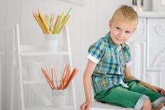 愉快的白肤金发的男孩孩子画象坐椅子 免版税库存照片