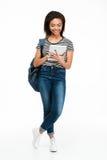愉快的相当十几岁的女孩佩带的背包和使用个人计算机片剂 免版税库存照片