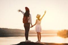 愉快的看天空的母亲和女儿在日落期间 免版税库存照片