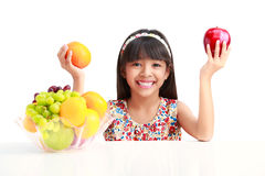 愉快的矮小的亚裔女孩坐与果子板材的桌  免版税库存照片