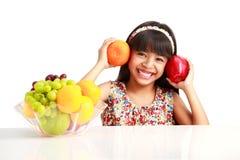 愉快的矮小的亚裔女孩坐与果子板材的桌  免版税库存图片