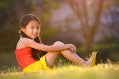 愉快的矮小的亚裔女孩坐草 免版税库存图片