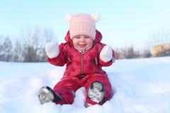 愉快的矮小的可爱的女婴在室外温暖的衣裳的11个月 免版税库存照片