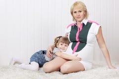 愉快的矮小的女儿在地毯说谎并且拥抱腹部 免版税库存照片
