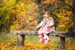 愉快的矮小的女婴坐笑和使用与叶子的长凳 本质上,露天走 免版税图库摄影