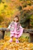 愉快的矮小的女婴坐笑和使用与叶子的长凳 本质上,露天走 库存图片