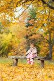 愉快的矮小的女婴坐笑和使用与叶子的长凳 本质上,露天走 免版税库存照片