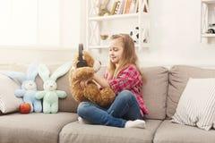 愉快的矮小的女孩和她的在家听到在沙发的音乐的玩具熊 免版税库存照片