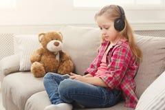愉快的矮小的女孩和她的在家听到在沙发的音乐的玩具熊 库存照片