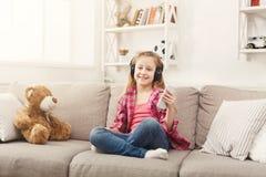 愉快的矮小的女孩和她的在家听到在沙发的音乐的玩具熊 图库摄影