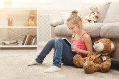 愉快的矮小的女孩和她的玩具熊阅读书在地板上在家 免版税库存照片