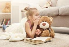 愉快的矮小的女孩和她的玩具熊阅读书在地板上在家 免版税库存图片