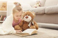 愉快的矮小的女孩和她的玩具熊阅读书在地板上在家 库存照片