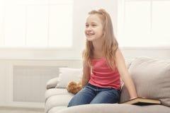愉快的矮小的女孩和她的玩具熊阅读书在沙发在家 免版税库存图片