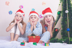 愉快的矮小的微笑的男孩和女孩有圣诞节帽子的 免版税图库摄影