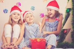 愉快的矮小的微笑的男孩和女孩有圣诞节帽子的 库存照片