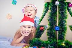 愉快的矮小的微笑的男孩和女孩有圣诞节帽子的 库存图片