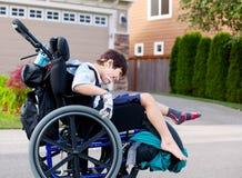 愉快的矮小的残疾男孩户外在轮椅 免版税图库摄影