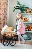 愉快的矮小的白肤金发的女孩在家使用与一辆婴儿推车在儿童` s屋子,在门或幼儿园 免版税图库摄影