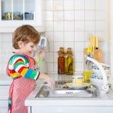 愉快的矮小的白肤金发的孩子男孩洗涤的盘在国内厨房里 图库摄影