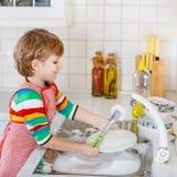 愉快的矮小的白肤金发的孩子男孩洗涤的盘在国内厨房里 免版税库存图片