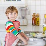 愉快的矮小的白肤金发的孩子男孩洗涤的盘在国内厨房里 免版税图库摄影