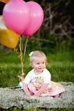 愉快的矮小的白肤金发的白种人女孩外面与气球 免版税图库摄影