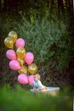 愉快的矮小的白肤金发的白种人女孩外面与气球 免版税库存图片