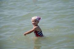 愉快的矮小的迷人的孩子在海沐浴 库存图片