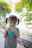 愉快的矮小的逗人喜爱的可爱的女孩中国儿童微笑笑打击气球获得乐趣在夏天公园自然幸福童年 库存照片