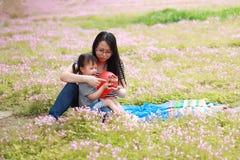 愉快的矮小的逗人喜爱的女婴微笑和戏剧迅速增加与母亲,妈妈讲故事给他的夏天公园愉快的家庭的女儿 免版税库存照片