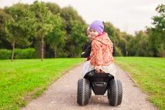 愉快的矮小的逗人喜爱的女孩乘坐摩托车外面 库存照片