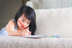 愉快的矮小的逗人喜爱的女孩在Th写着与红色铅笔的书 免版税库存图片