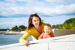 愉快的矮小的婴孩和微笑的母亲由海 库存图片