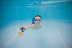 愉快的矮小的婴孩在与行动照相机的水池游泳在水面下 在水下的射击 横向取向 库存图片