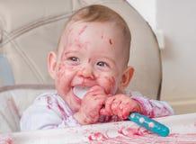 愉快的矮小的婴孩是吃和舔从匙子的快餐 图库摄影