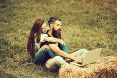 愉快的研究膝上型计算机的女孩容忍有胡子的人行家 库存照片