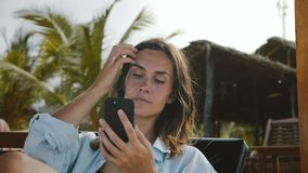 愉快的确信的女实业家在海滩躺椅使用智能手机移动式办公室应用程序坐度假村 股票视频