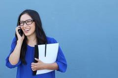 愉快的确信的女实业家谈话在蓝色隔绝的流动手机 免版税图库摄影