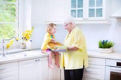 愉快的祖母和女孩烘烤饼在白色厨房里 免版税库存图片