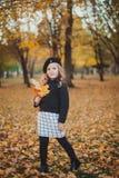 愉快的秋天 一顶红色贝雷帽的一个小女孩使用与落的叶子和笑 免版税库存照片